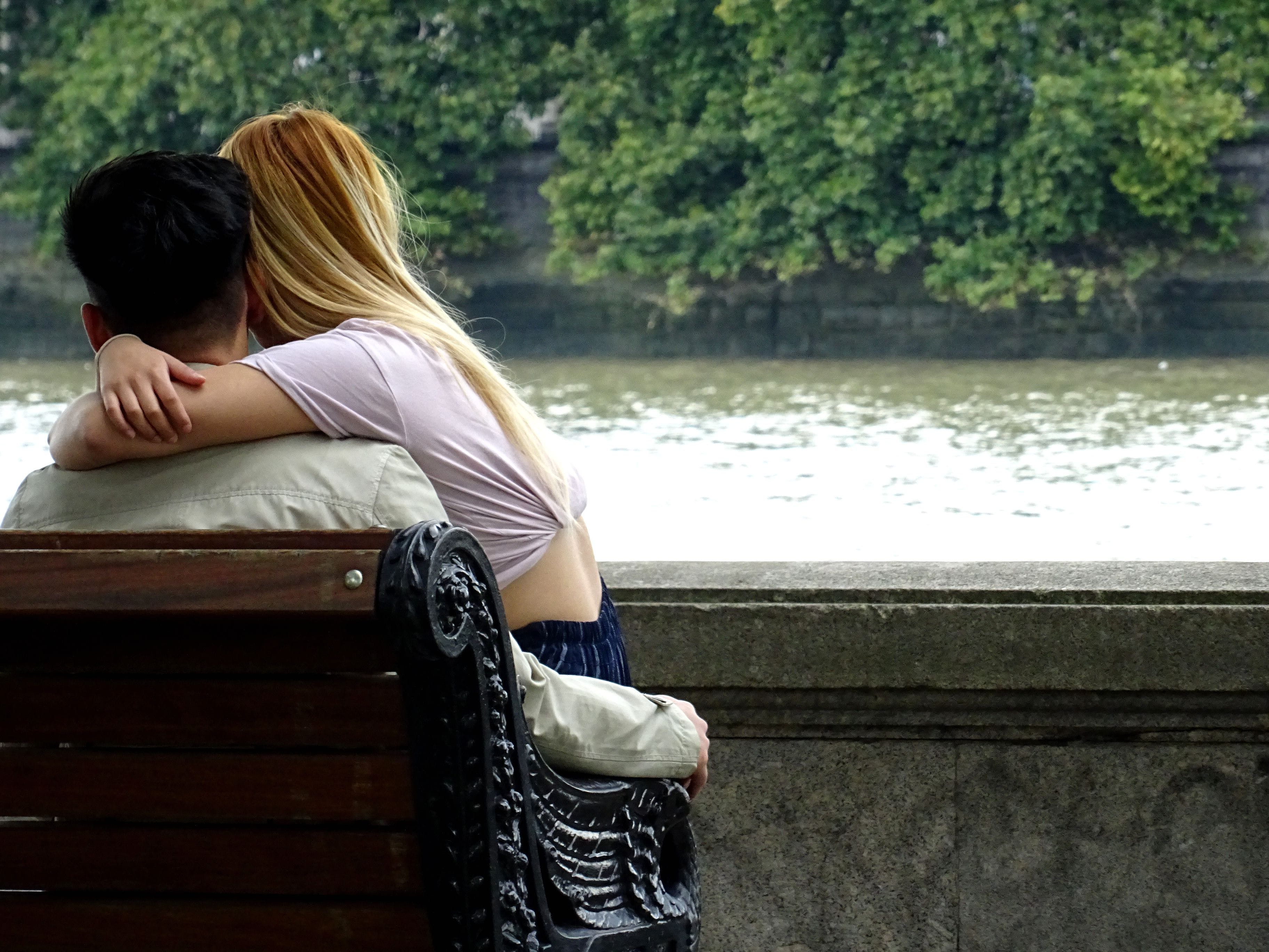 Man and Woman Sitting on Bench With River View