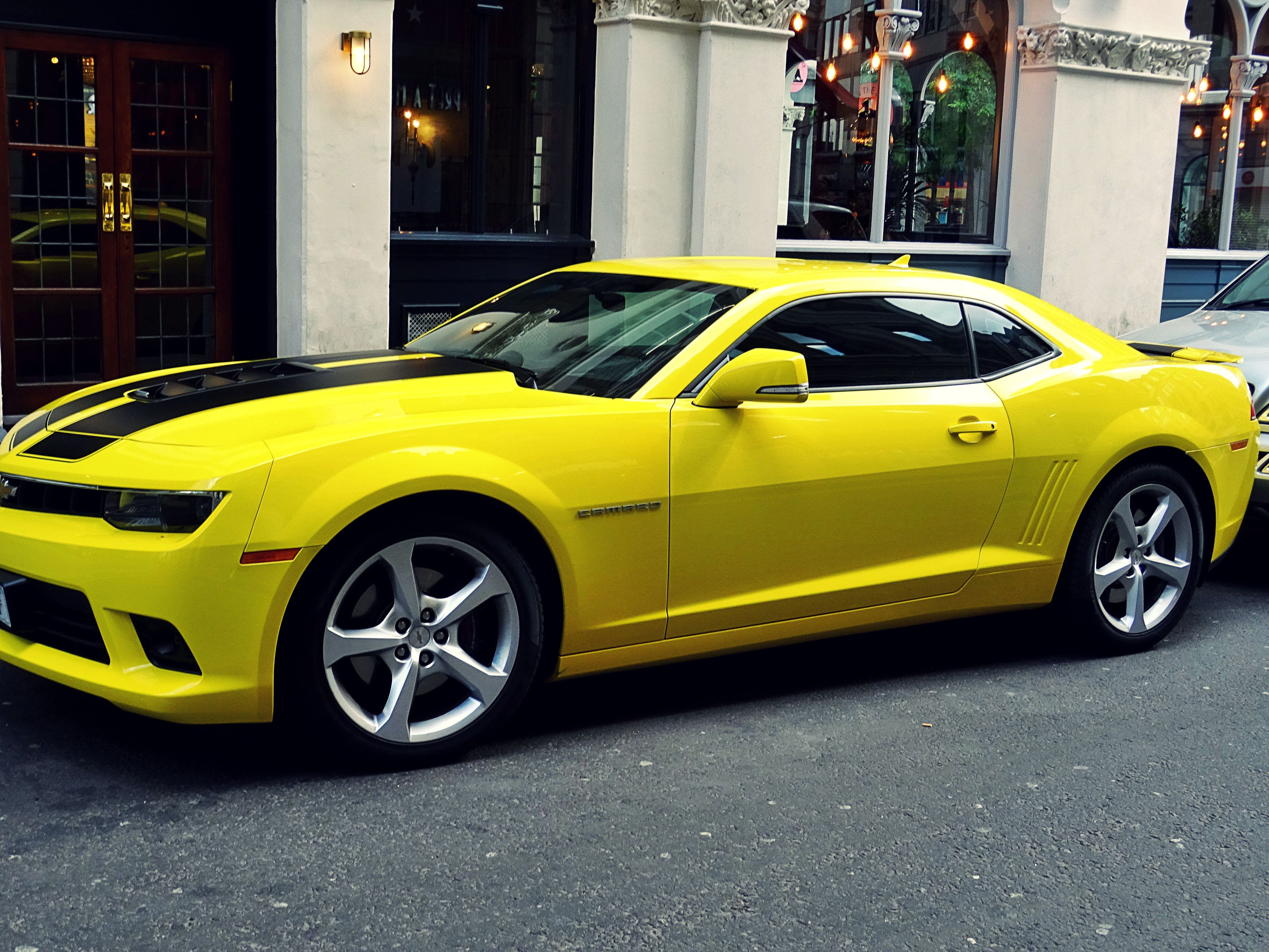Yellow Chevroelt Camaro Parked Outside of Building