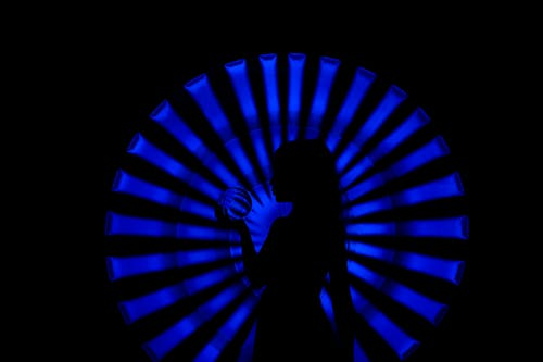 Side view silhouette of unrecognizable female with long hair standing in dark room with crystal ball in hand near bright neon blue illumination