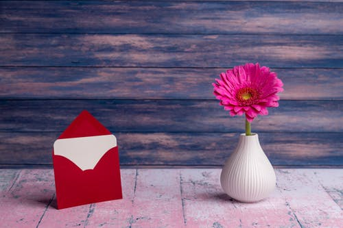 Small vase with pink Gerbera jamesonii flower arranged with postcard placed in red envelope on wooden table