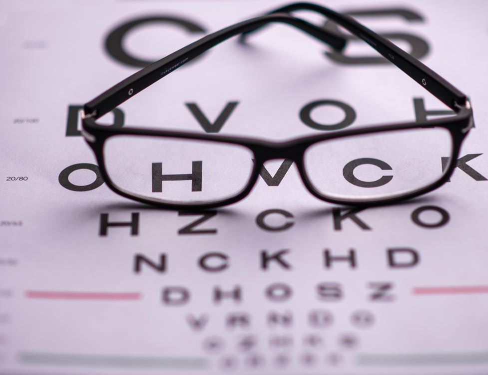 From above of classic eyeglasses placed on eye chart with letters in ophthalmologist room