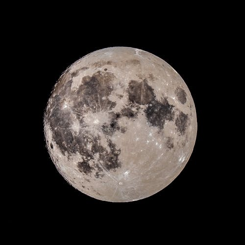 From below of black and white of full moon with craters shining in dark endless sky at night