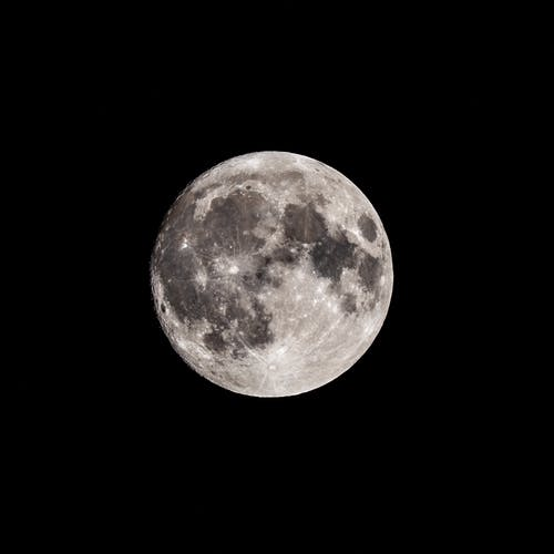 Low angle of black and white bright shiny full moon in dark night sky