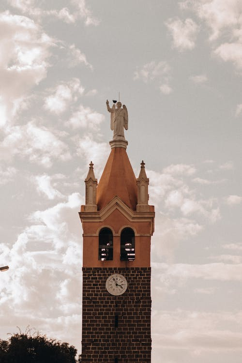 Aged tower with brick wall and statue of angel on roof against cloudy sky