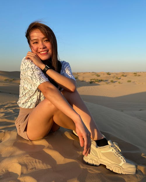 Full body of cheerful young Asian female traveler in trendy outfit sitting on sandy dune and smiling while enjoying sunny day in desert