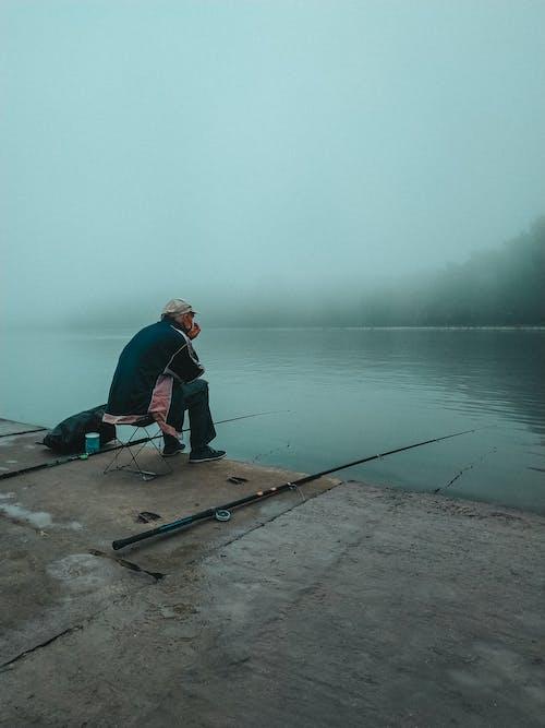 Man in Blue Jacket Fishing on Lake