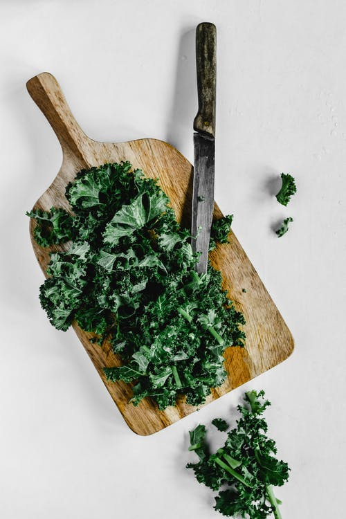 Close-Up Shot of Chopped Kale on a Wooden Chopping Board