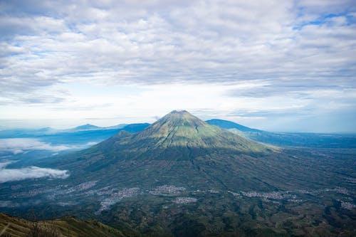 Volcanic mountain peak under cloudy sky