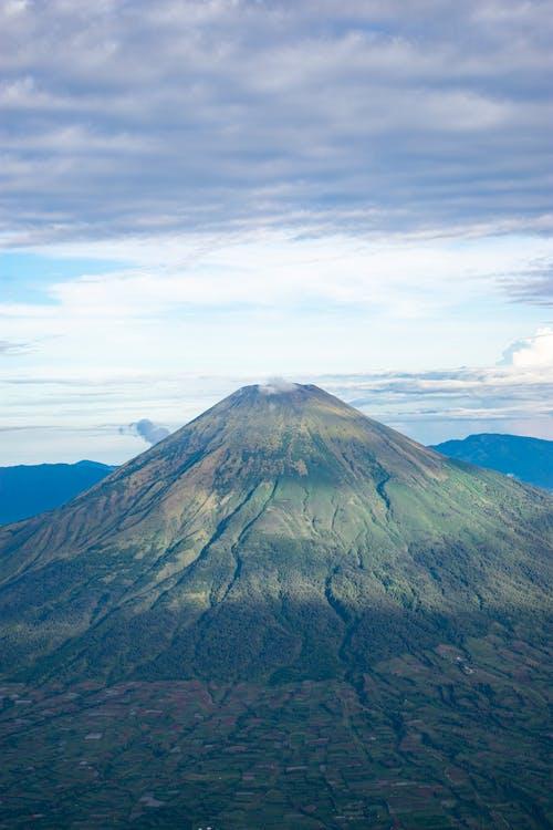 Dormant volcano under bright cloudy sky
