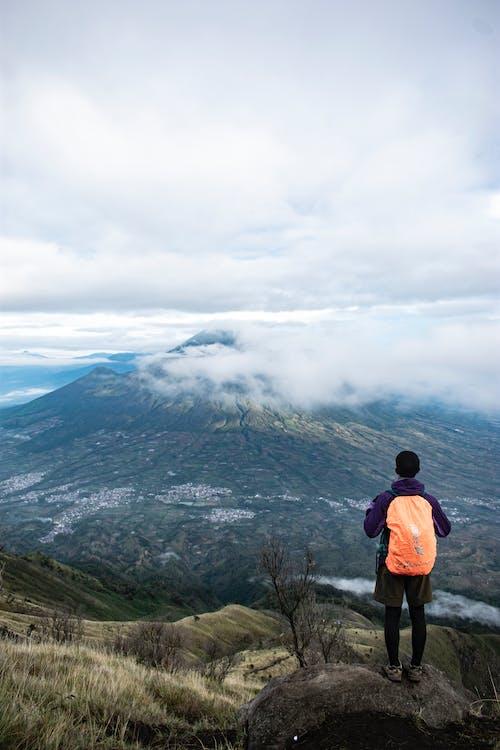 Unrecognizable traveler standing against volcanic mountain