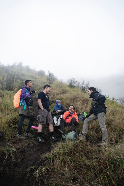Full body of diverse group of travelers with backpacks relaxing on grassy hillside during hiking in highlands