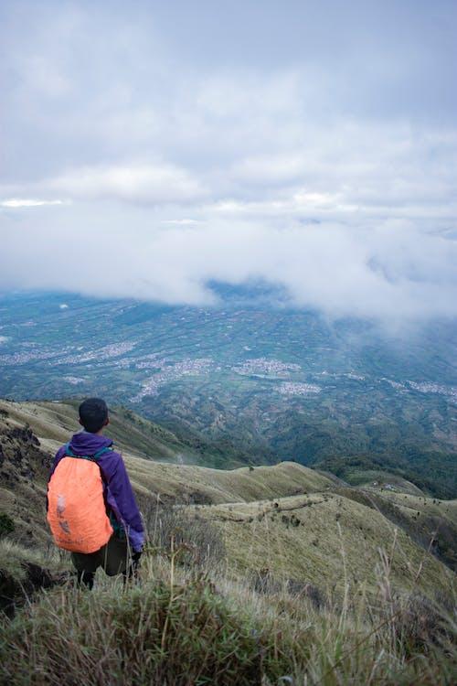 Anonymous man standing on mountain peak