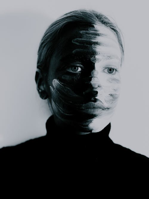 Emotionless young lady with smears on painted face looking away in studio