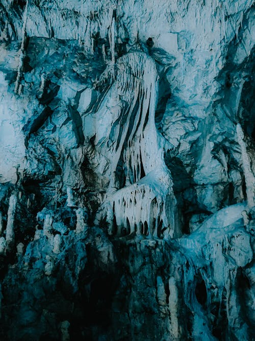 Icicles hanging on rough surface of rocky formation in dark cave in winter