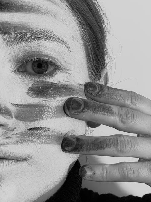 Crop black and white melancholic female smearing dark paint on face with artistic makeup and looking at camera