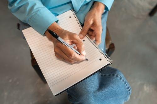 Человек в синих джинсовых джинсах держит черную ручку и пишет на белом блокноте