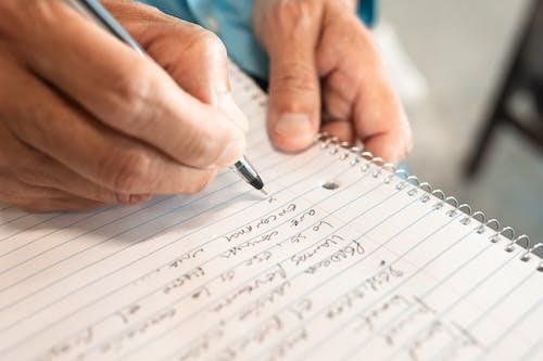 Человек, пишущий на белой бумаге в линейку