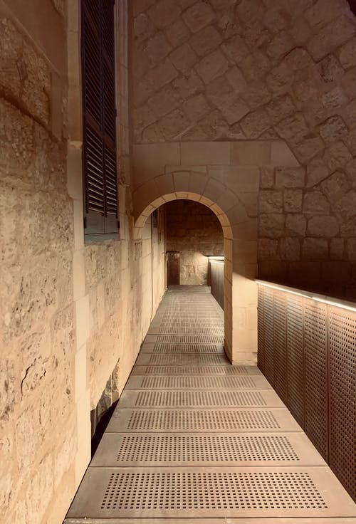Empty narrow corridor with arch and shuttered window on shabby stone walls in old building