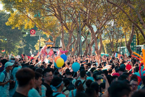 Crowd of unrecognizable Asian people standing on city street with colorful balloons and watching performance during festival on sunny day