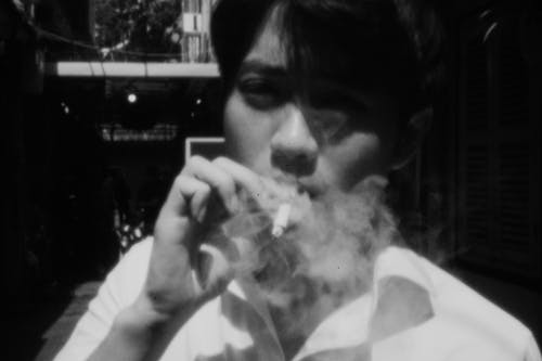 Black and white of crop young Asian guy in shirt smoking cigarette on street on sunny day and looking at camera