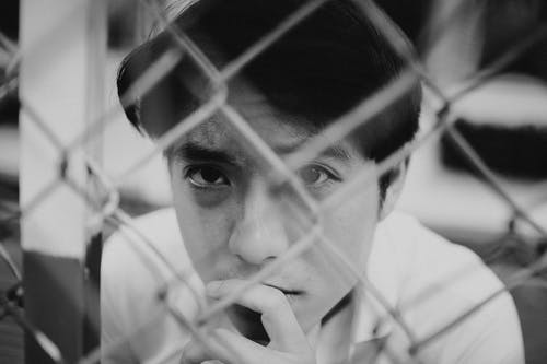 Pensive young Asian man looking at camera through metal net fence