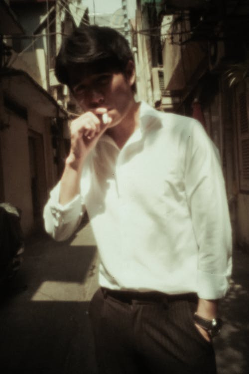Confident young ethnic male in white shirt chilling on narrow street with hand in pocket and smoking cigarette on sunny day