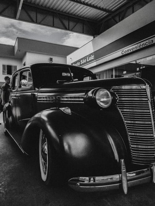 Black and white shiny old fashioned car with chrome details under roof in garage