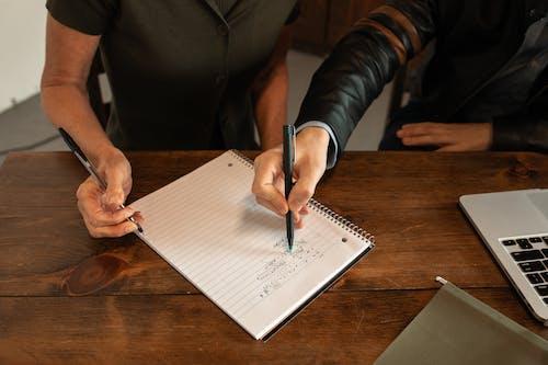 Gratis lagerfoto af hænder, kuglepenne, notesbog med spiralryg