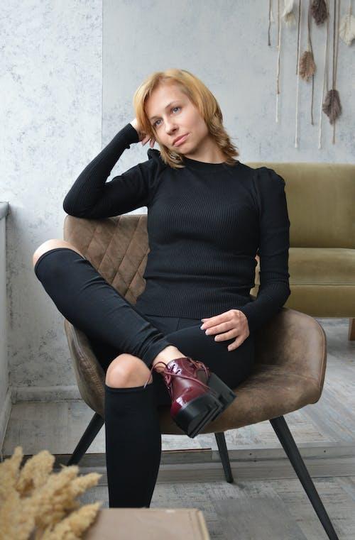 Thoughtful stylish woman sitting on chair