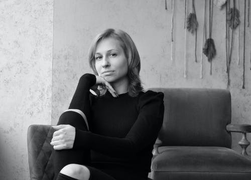 Black and white of calm young female looking at camera pensively while relaxing on chair in living room