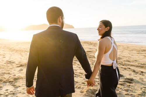 Man and Woman Holding Hands While Walking on Beach