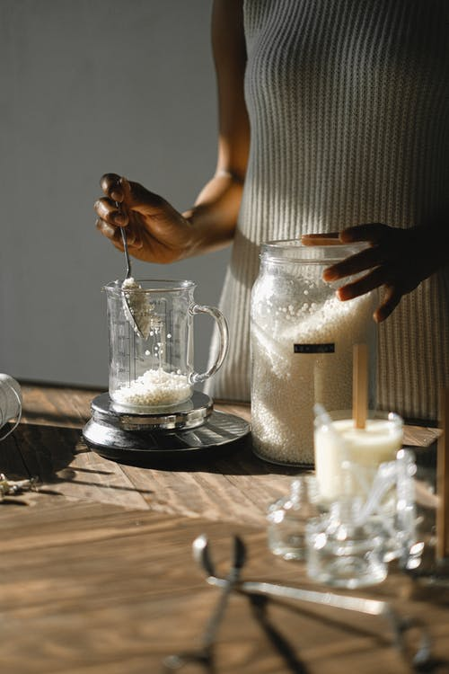 Crop black woman pouring wax into jug