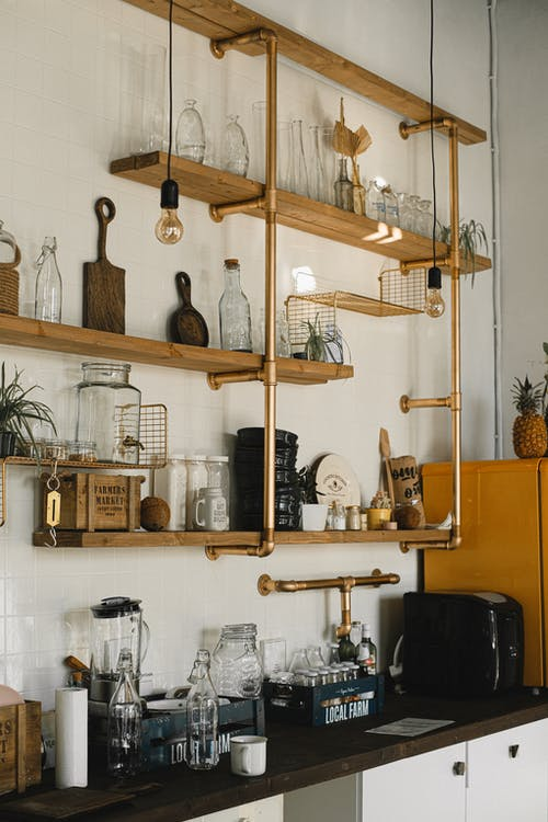Interior of kitchen with different glass bottles and kitchenware placed on timber shelves