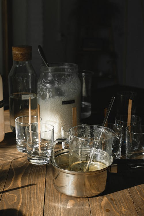 Glassware and pot with melt wax for candle making