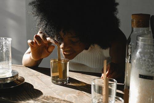 Woman Smelling A Liquid Mixture