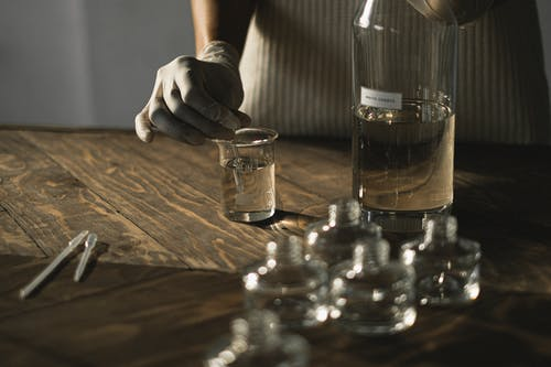 Crop anonymous female in latex gloves making fluid for perfume among glass jars on wooden table