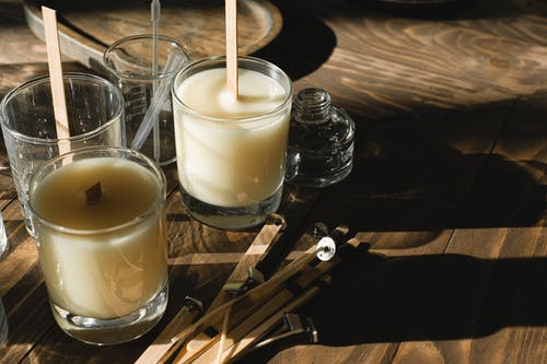 Glasses with organic candles on wooden table