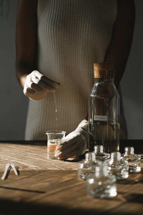 Woman Pouring Liquid on Clear Glass Bottle