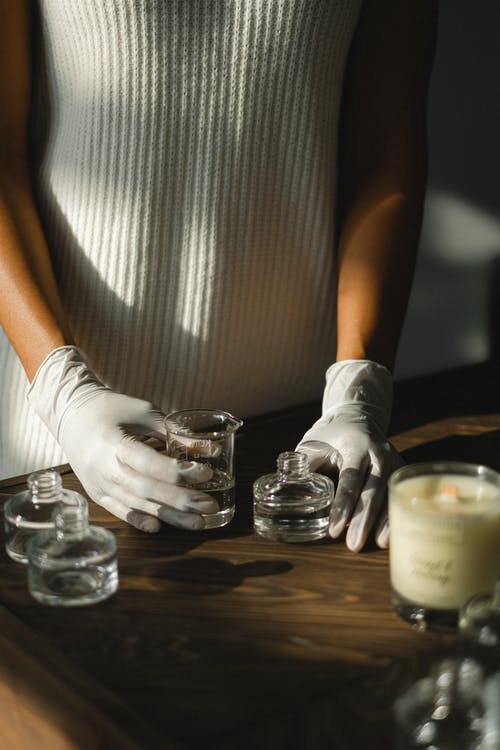 Black woman in latex gloves making aromatic diffuser