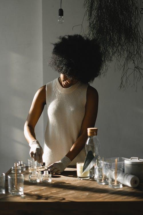 Black woman making liquid incense in workshop