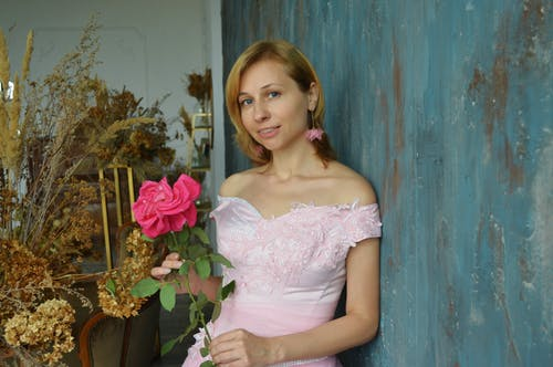 Elegant woman in pink gown with flower