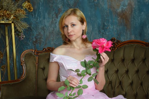 Beautiful young female in elegant pink lace gown and earrings holding delicate rose flower and looking at camera while sitting on vintage sofa