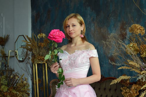 Smiling young bride with pink flower