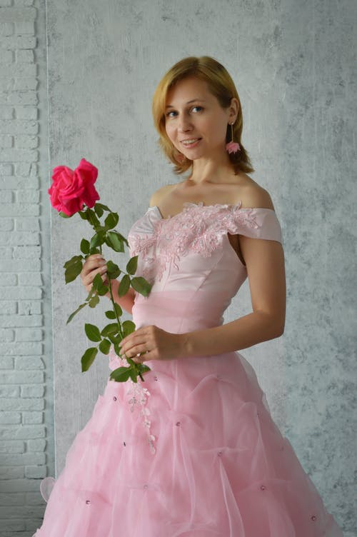 Graceful young female in charming pink bridal gown and earrings with rose flower in hands smiling and looking at camera while standing against gray wall