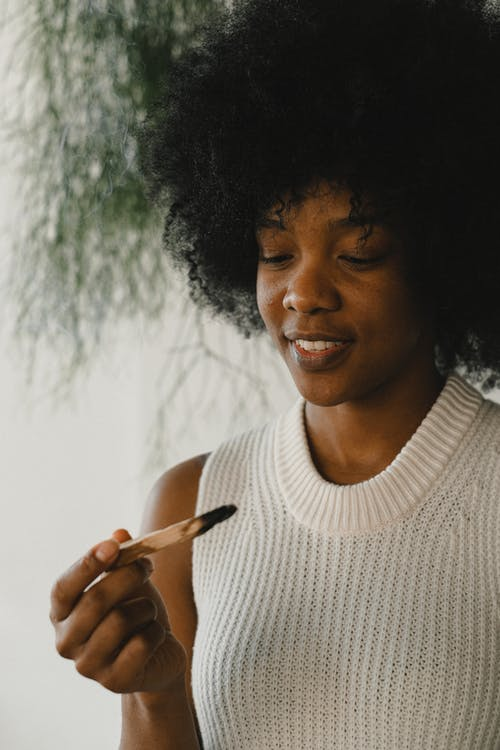 Glad African American female with curly hair enjoying aromatic palo santo stick during aromatherapy at home