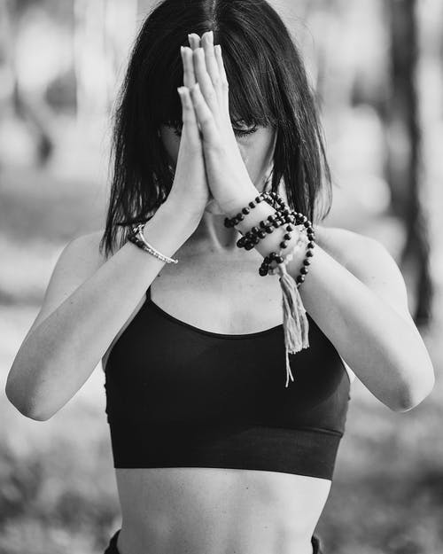 Black and white of concentrated lady in sports bra meditating with prayer hands in nature
