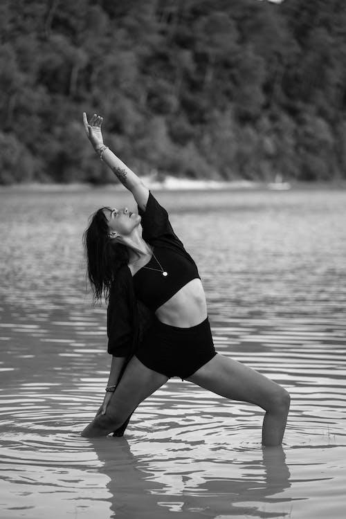 Monochrome tranquil lady practicing yoga asana Virabhadrasana in water