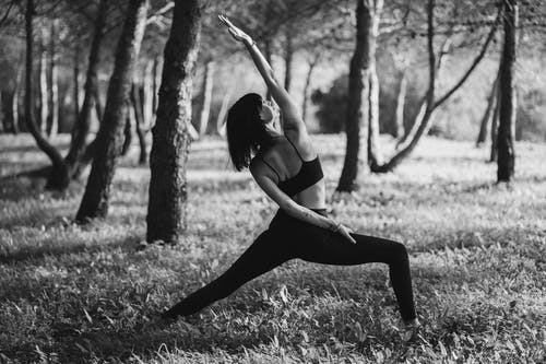 Black and white of anonymous barefoot woman in sportswear doing yoga asana in park in daylight