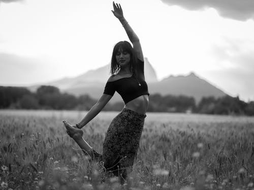 Cheerful lady doing yoga in field