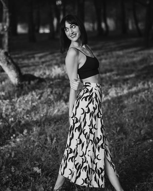 Black and white of happy lady in long ornamental skirt strolling in park in daylight